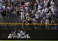 Colorado Rockies center fielder Carlos Gonzalez, bottom center,is taken off the field after he collided with the wall on a fly ball in the seventh inning of an interleague baseball game against the Kansas City Royals in Denver on Sunday, July 3, 2011. The Royals won 16-8. (AP Photo/Chris Schneider)