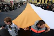 "Russian ultra-nationalists hold a giant pre-revolutionary flag as they take part in the so-called ""Russian March"" in central Moscow on November 4, marking the National Unity Day. Alexander Belov, one of the march's organisers, said the participants were growing disillusioned with President Vladimir Putin. ""Putin is the head of the criminal regime,"" Belov told reporters. ""They are tired of him."""