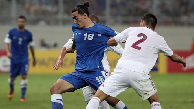 Greece's Lazaros Christodoulopoulos, left, and Latvia's Vitalijs Maksimenko challenge for the ball during their World Cup Group G qualifying soccer match at the Karaiskaki stadium in Piraeus port, near Athens, on Tuesday, Sept. 10, 2013