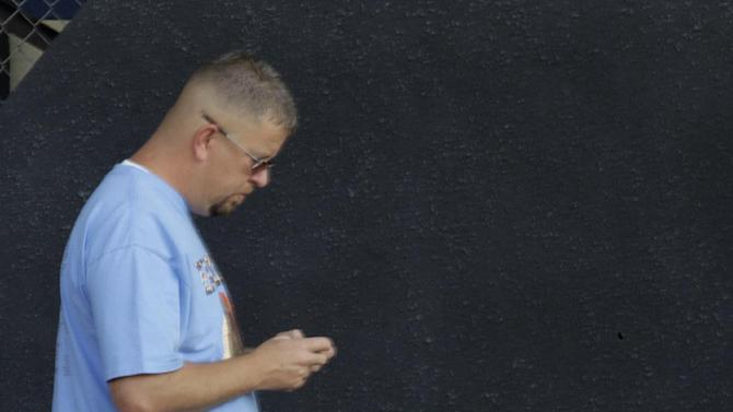 A visitor to the Indiana State Fair on opening day sends a text on his phone beside the memorial to the seven killed in the Aug. 13, 2011 stage collapse during a Sugarland concert at the fair in Indianapolis, Aug. 3, 2012. The memorial was virtually unnoticed by fair visitors. (AP Photo/Michael Conroy)