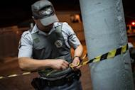 A police officer cordons off a crime scene in Sao Paulo, Brazil, on November 14, 2012. Officers are investigating after a 13-year-old Brazilian boy killed his parents, grandmother and great-aunt