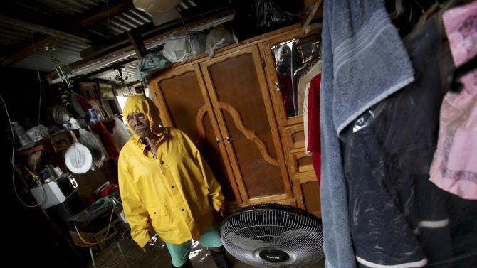 Ismael Vela Hernandez, 60, stands inside his flooded home after heavy rains caused by Tropical Storm Barry in the city of Veracruz, Mexico, Thursday June 20, 2013. Barry has weakened to a tropical depression but is still producing torrential rains. (AP Photo/Felix Marquez)