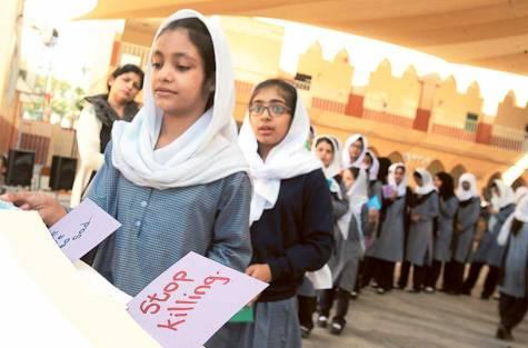 Pupils and officials at Shaikh Rashid Al Maktoum Pakistani School perform a funeral prayer yesterday for the victims of the Peshawar school attack