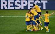 Swedish players celebrate after midfielder Sebastian Larsson scored a goal during the Euro 2012 football championships match Sweden vs France at the Olympic Stadium in Kiev. France qualified for the knockout stages of a major finals for the first time in six years here on Tuesday despite losing their final Euro 2012 Group D match 2-0 to already eliminated Sweden