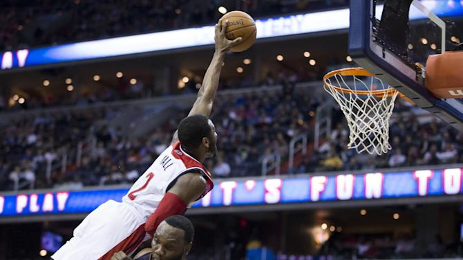 Charlotte Bobcats center Al Jefferson  draws an offensive foul from Washington Wizards guard John Wall during the second half of an NBA basketball game Wednesday, March 12, 2014, in Washington. The Bobcats defeated the Wizards 98-85
