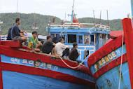 In this photo taken Wednesday, June 10, 2015 and released by the Government of the Republic of Palau, Vietnamese fishermen sit on their fishing ship anchored at the Marine Law Enforcement Division Port in Koror, Palau after being caught fishing illegally in the waters of the country. The tiny Pacific nation of Palau, fighting a rising tide of illegal fishing in its waters, has set fire to four boats of Vietnamese caught poaching sea cucumbers and other marine life in its waters. Palau's president, Tommy Remengesau Jr., said the boats were burned Friday morning, June 12, 2015. He hopes to turn most of the island nation's territorial waters into a national marine sanctuary, banning commercial fishing and exports apart from limited areas to be used by domestic fishermen and tourists. (The Government of the Republic of Palau via AP)