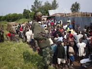 A rebel of the M23 group talks to residents after their troops entered the town of Rutshuru near the Ugandan border on July 8, 2012. DR Congo authorities and the United Nations fear that the M23 movement, which took one town on the Uganda border last week and forced 600 government troops to flee, may target the provincial capital of Goma, UN officials said