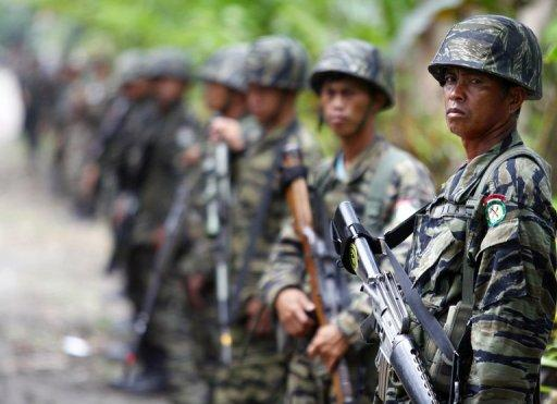Moro Islamic Liberation Front (MILF) rebels stand guard as their chief Murad Ebrahim (not pictured) holds a press conference inside camp Darapanan, Sultan Kudarat town on October 27. Under the pact the 12,000-strong MILF would give up its quest for an independent homeland in the south in return for significant power and wealth-sharing in a new autonomous region there to be known as Bangsamoro