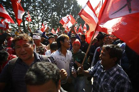 Supporters of the Nepali Congress Party cheer for their party as the Constituent Assembly Election scores are displayed on a screen outside the Constitution Assembly Building in Kathmandu November 21, 2013. REUTERS/Navesh Chitrakar