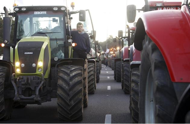 Farmers drive their tractors on the highway leading to Paris, Thursday, Sept.3, 2015. Hundreds of tractors were descending on Paris on Thursday in a boisterous protest by farmers blocking highways to