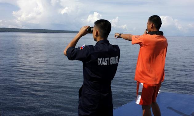 Philippine Coast Guard coast guard officers scan the horizon for survivors of the Our Lady of Mount Carmel ferry sinking off Burias Island on June 15, 2013. Philippine authorities said they had abandoned hope of finding alive seven people missing from a ferry which sank last week with dozens on board, after three days of searching in strong currents