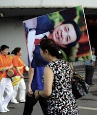"""File photo shows a Chinese woman in Chongqing carrying a protrait of Bo Xilai after a """"red"""" culture session, where workers gather to sing revolutionary songs. Bo, until recently a rising political star, was known in for busting gangs and reviving Maoist ideals in Chongqing"""