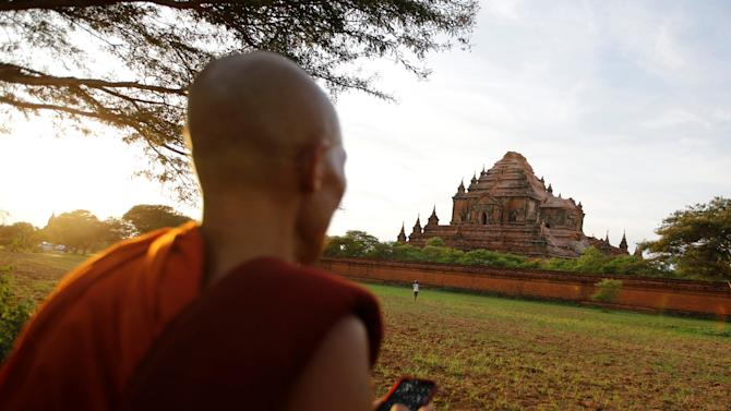 A Buddhist monk looks at a damaged pagoda after an earthquake in Bagan