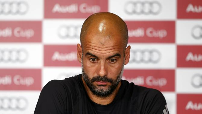 Coach Guardiola of Bayern Munich reacts during a news conference on the eve of their pre-season Audi Cup tournament, in Munich
