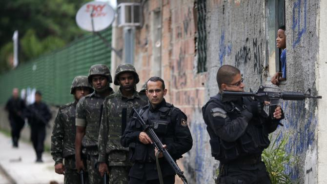 Policemen take position as they assist Brazilian Army soldiers during a operation in the Mare slums complex in Rio de Janeiro