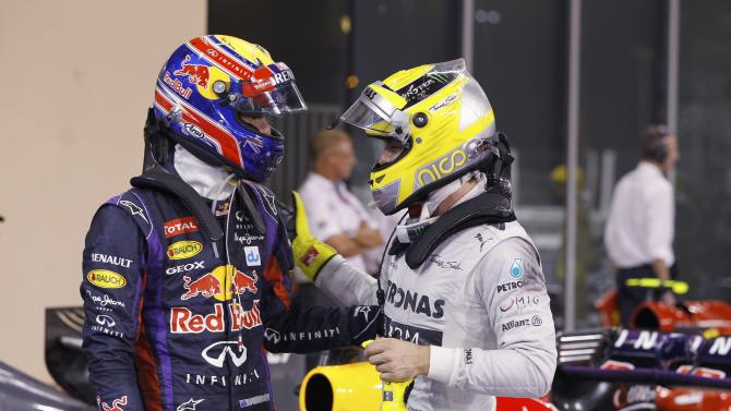 Red Bull Formula One driver Webber of Australia is congraluted by Mercedes Formula One driver Rosberg of Germany after the qualifying session of the Abu Dhabi F1 Grand Prix at the Yas Marina circuit on Yas Island