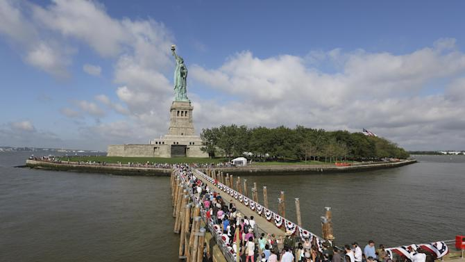 Visitors to the Statue of Liberty disembark onto Liberty Island from the first ferry to leave Manhattan, Thursday, July 4, 2013, in New York. The Statue of Liberty finally reopened on the Fourth of July months after Superstorm Sandy swamped its little island in New York Harbor as Americans across the country marked the holiday with fireworks and barbecues. (AP Photo/Mary Altaffer)