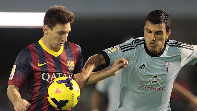 Barcelona's Lionel Messi from Argentina, left, fights for the ball with RC Celta's Gustavo Cabral from Argentina, right, during a Spanish La Liga soccer match at the Balaidos stadium in Vigo, Spain, Tuesday, Oct. 29, 2013