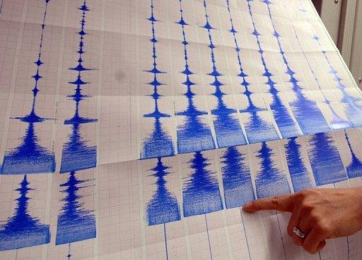A seismologist points to a graphic showing an earthquake at a monitoring centre