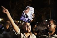 Supporters express their anger outside the ransacked headquarters of presidential candidate Ahmad Shafiq in Cairo