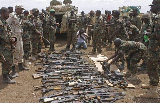AU soldiers from Uganda look at weapons recovered from members of Somalia's Al-Qaeda-linked Shebab after they gave themselves up in Garsale, some 10km from Jowhar, in September 2012. African Union troops and Somali forces seized the formerly Islamist-held town of Jowhar Sunday, wresting control of one of the largest remaining towns held by the Shebab, officials said.