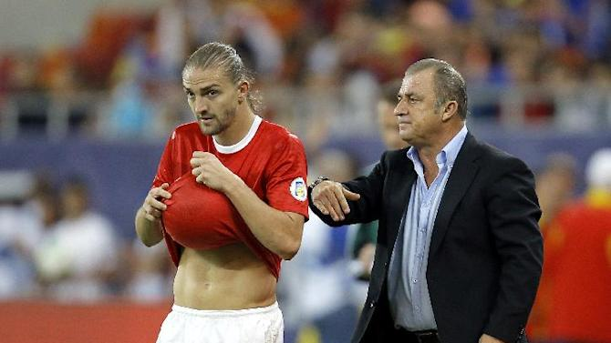 Turkey's coach Fatih Terim, right, gestures as Caner Erkin, left, wipes the ball with his shirt during a World Cup Group D qualifying soccer match between Romania and Turkey at the National Arena stadium in Bucharest, Romania, Tuesday, Sept. 10, 2013