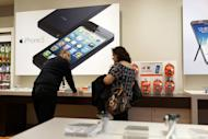 Advertisements for the iPhone 5 are displayed at an mobile phone store on January 14, 2013 in New York City. Apple dethroned Samsung as the top US mobile phone vendor in the final quarter of last year, claiming a record share of 34 percent, research firm Strategy Analytics reported Friday