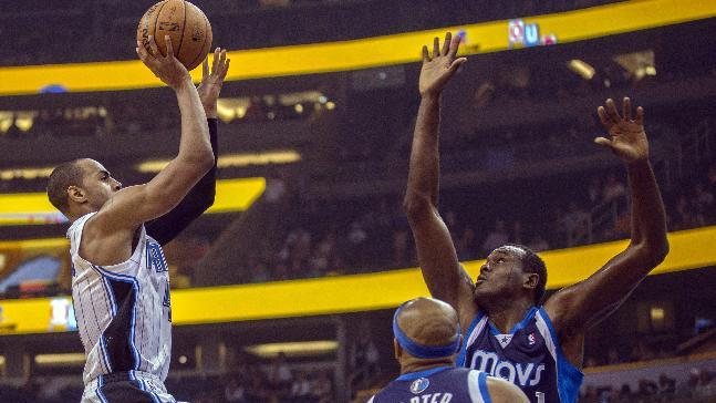 Orlando Magic's Arron Afflalo, left, shoots over the Dallas Maverics' Vince Carter and Samuel Dalembert, right, during the first half of an NBA basketball game in Orlando, Fla., Saturday, Nov. 16, 2013