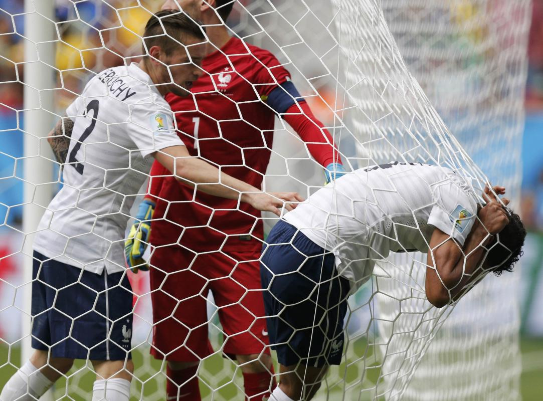 France's Varane clings on to the goal net as he reacts to an injury beside teammates Debuchy and goalkeeper Lloris during their 2014 World Cup...