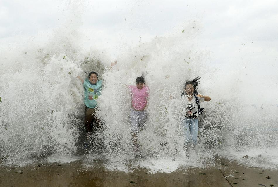 Tourists standing near the sea shore are hit by a wave, which surged past a barrier under the influence of Typhoon Chan-hom, in Qingdao