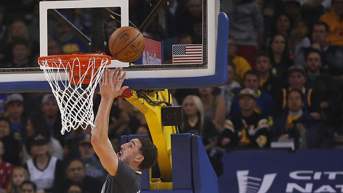 Golden State Warriors guard Klay Thompson (11) drives to the basket past Sacramento Kings guard Ben McLemore (23) during the first half of an NBA basketball game Saturday, Nov. 28, 2015, in Oakland, Calif. (AP Photo/Tony Avelar)