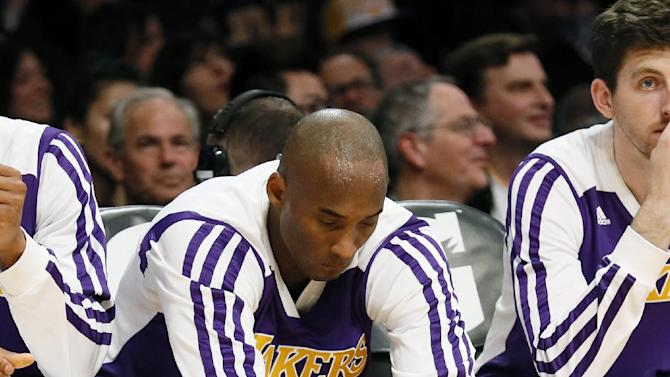 Los Angeles Lakers' Kobe Bryant stretches on the bench against the Toronto Raptors during the first half of an NBA basketball game in Los Angeles, Sunday, Dec. 8, 2013. It was Bryant's first game back after a torn left Achilles tendon injury on April 12th