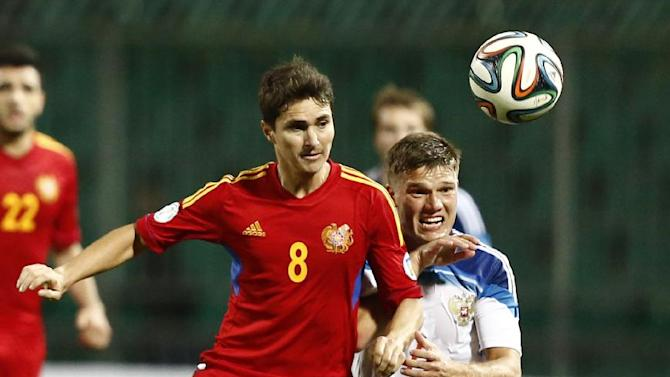 Russia's Igor Denisov, right, competes for a ball with Armenia's Marcos Pizzelli during international friendly soccer match in Krasnodar, Russia, Wednesday, March 5, 2014. Russia won 2-0
