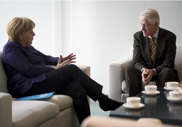 German Chancellor Merkel speaks with former U.S. President Clinton in her office at the Chancellery in Berlin