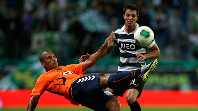 Sporting's Cedric Soares, right, watches  Setubal's Rafael Martins, from Brazil, clear the ball during their Portuguese league soccer match Saturday, Oct. 5 2013, at Sporting's Alvalade stadium in Lisbon