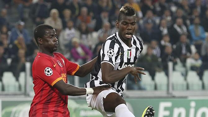 Juventus midfielder Paul Pogba, right, of France, challenges for the ball with Galatasaray defender Emmanuel Eboue, of Ivory Coast, during a Champions League, Group B, soccer match  at the Juventus stadium in Turin, Italy, Wednesday, Oct. 2, 2013