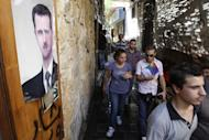 People walk past a poster featuring Syrian President Bashar al-Assad in the capital Damascus on September 16, 2013