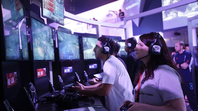 """Fanny Bouton, right, plays the """"Need for Speed"""" racing video game at the EA booth during the Electronic Entertainment Expo in Los Angeles, Wednesday, June 12, 2013. (AP Photo/Jae C. Hong)"""