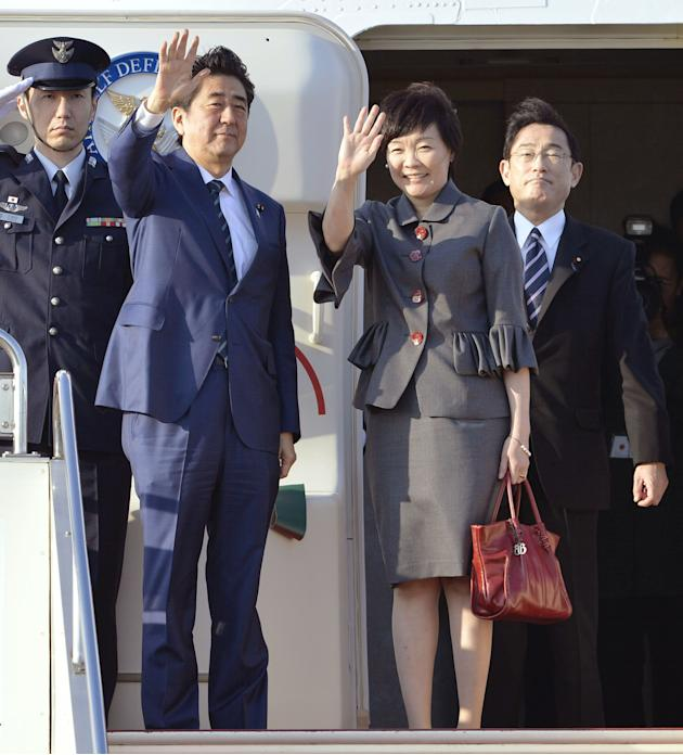 Japanese Prime Minister Shinzo Abe, second left, and his wife, Akie, wave as they leave for the United States at Tokyo's Haneda International Airport Sunday, April 26, 2015. Abe's itinerary fo