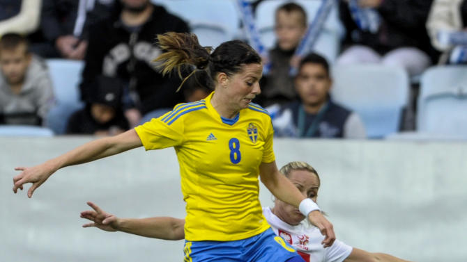 Sweden's Lotta Schelin, front, vies for the ball with Poland's Patrycja Pozerska, back, during the ladies' football World Championships qualification match at Swedbank Stadium in Malmo, Sweden, Saturday September 21, 2013. (AP Photo / Scanpix Sweden, Bjorn Lindgren)
