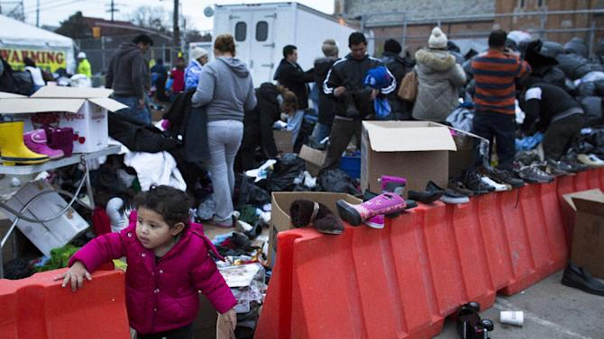 A young girl plays as residents search through donated clothing piles in the Rockaways, Saturday, Nov. 10, 2012, in the Queens borough of New York. Despite power returning to many neighborhoods in the metropolitan area after Superstorm Sandy crashed into the Eastern Seaboard, many residents of the Rockaways continue to live without power and heat due to damage caused by Sandy. (AP Photo/John Minchillo)