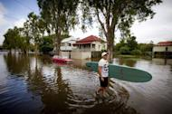 A man rescues a surfboard from a flooded home in the inner Brisbane suburb of Newmarket on January 28, 2013 as high winds and heavy rains brought by ex-tropical cyclone Oswald hit the state of Queensland. The floods have claimed four lives -- the most recent a three-year-old boy killed by a falling tree