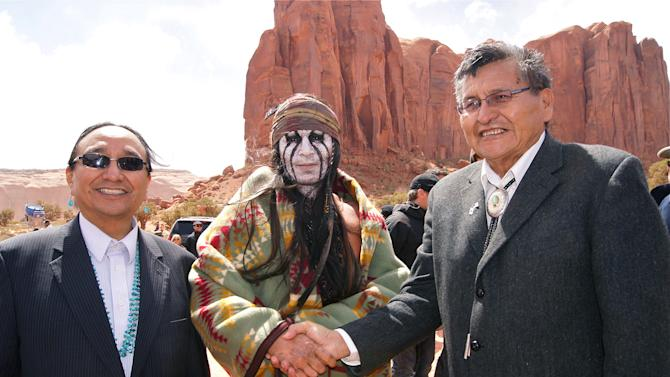 "This April 2012 photo released by the Navajo Nation shows, actor Johnny Depp, center, shaking hands with Navajo Nation President Ben Shelly and Navajo Nation Vice President Rex Lee Jim in Monument Valley during the filming of ""The Lone Ranger."" The Pendleton blanket was presented to Johnny Depp as a good will gesture on behalf of the Navajo Nation.  (AP Photo/Emerald Craig, Navajo Nation)"