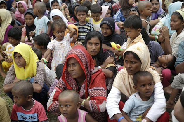 Ethnic Rohingya women and children gather to receive meal at a temporary shelter in Bayeun, Aceh province, Indonesia, Saturday, May 23, 2015. More than 3,000 migrants abandoned by human traffickers ha