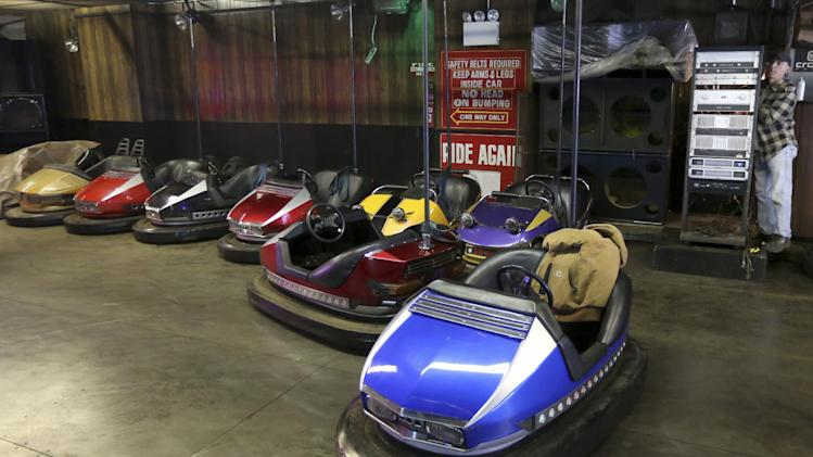 In a Saturday March 30, 2013, photo  an employee repairs the bumper car ride at Eldorado Auto Skooter at New York's Coney Island.  Despite making the traditional Palm Sunday opening, many of the seasonal businesses at Coney Island are still reeling from the aftermath of Superstorm Sandy. (AP Photo/Mary Altaffer)