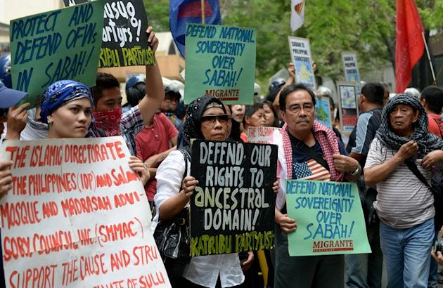 Protesters hold placards as they attend a rally in front of the Malaysian embassy in Manila on March 5, 2013 over the crackdown by Malaysian security forces against a group of followers of a self-proclaimed Philippine sultan who entered the Malaysian state of Sabah to assert the sultan's claim over the area. Malaysia, facing its worst security crisis in years, insists the gunmen must surrender