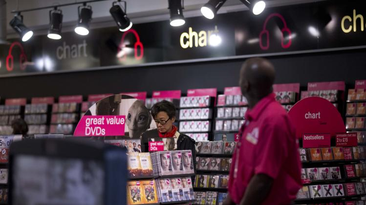 A woman looks at items for sale at a branch of HMV on Oxford Street in London, Tuesday, Jan. 15, 2013.  British music and entertainment retailer HMV admitted defeat on Tuesday after more than 90 years on the U.K high street, suspending trading in its shares and calling in administrators to try to salvage any viable parts of the business.  HMV is the last big retail chain selling recorded music in Britain and employs more than 4,000 people working in 238 stores, which will remain open for the time being. The company's management confirmed that it had failed to gain agreements with lenders and suppliers to continue trading.  (AP Photo/Matt Dunham)