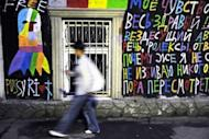 """A man walks past a grafitti in support of a punk band """"Pussy Riot"""" in central Moscow on August 12. Russian police on Wednesday arrested four activists who demonstrated outside a landmark Moscow church in support of members of protest punk band Pussy Riot who are now on trial"""