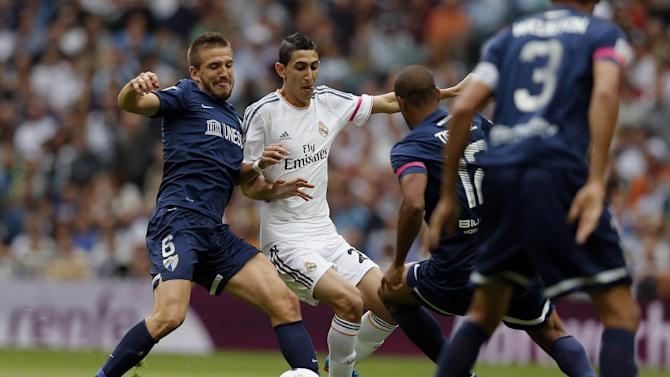 Real Madrid's Angel Di Maria from Argentina, second left, in action with Malaga's Camacho, left, during a Spanish La Liga soccer match at the Santiago Bernabeu stadium in Madrid, Spain, Saturday, Oct. 19, 2013