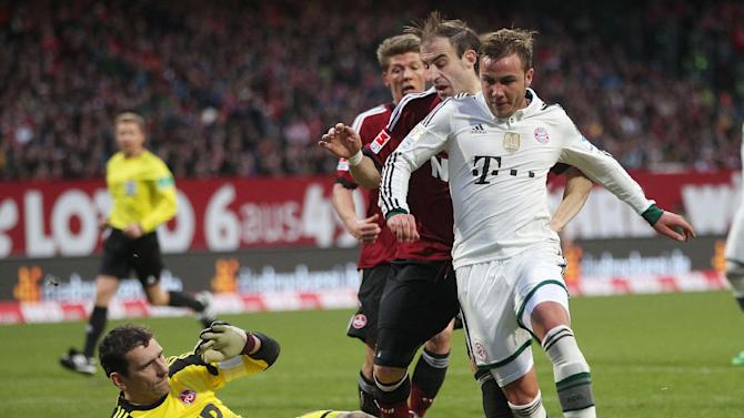 Nuremberg goalkeeper Raphael Schaefer, left, and Bayern's Mario Goetze challenge for the ball during a  German first  division Bundesliga soccer match  between 1.FC Nuremberg and Bayern Munich in Nuremberg, Germany, Saturday, Feb. 8, 2014